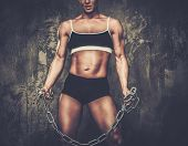 image of transexual  - Muscular bodybuilder woman holding chains - JPG