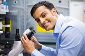 stock photo of histology  - Closeup portrait young friendly scientist looking into microscope - JPG