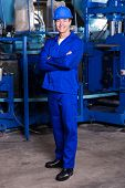 stock photo of blue-collar-worker  - blue collar industrial worker with arms crossed in factory - JPG