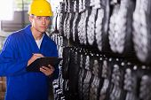 factory quality controller checking gumboots in warehouse