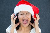 picture of scream  - Closeup portrait of a cute Christmas woman with a red Santa Claus hat white dress screaming out loud frustrated eyes shut in rage - JPG