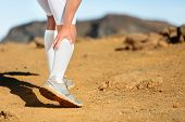 Running Cramps in leg calves or sprain calf on runner. Sports injury concept with running fitness man athlete outside.