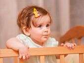 Small Child With A Hairpin Standing In Crib.
