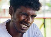 WELIGAMA, SRI LANKA - MARCH 7, 2014: Portrait of young local man winking for camera. Local people in