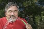 Hispanic man drinking from hose