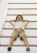 Hispanic boy laying on stairs