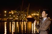 Asian businessman next to water at night