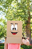 Woman with cardboard box on her head with happy face, outdoors