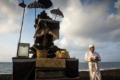 BALI, INDONESIA - SEPTEMBER 19, 2014: A priest performs the prayers for families at the Nyaben cerem