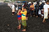 BALI, INDONESIA - SEPTEMBER 19, 2014: Two young girls pray at a the Nyaben 12th day ceremony, a day