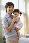 Asian father holding baby daughter