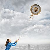 Young woman in casual catching clock with rope