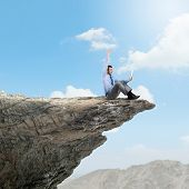 Young businessman sitting on edge of rock mountain and using tablet pc
