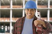 Hispanic construction worker holding level