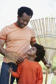 African father and son holding rakes