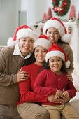 Hispanic family wearing Santa Claus hats