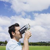stock photo of 35 to 40 year olds  - Mixed Race man looking through old fashioned film camera - JPG