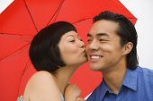 Asian woman kissing boyfriend on cheek