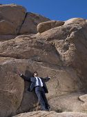African businessman leaning on rock