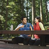 Indian couple drinking coffee in woods