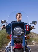Hispanic woman sitting on motorcycle