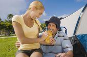 Hispanic woman feeding sandwich to boyfriend