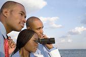 African businesspeople looking through binoculars