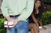 Hispanic man surprising girlfriend with gift