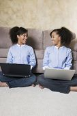 African twin sisters with laptops