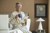 Hispanic man holding coffee and newspaper