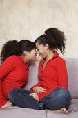 stock photo of identical twin girls  - African twin sisters rubbing noses - JPG