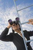 African businesswoman looking through binoculars on ladder