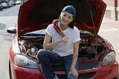 Asian woman sitting next to open car hood