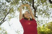 Hispanic woman with arms raised