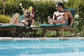 Multi-ethnic couple relaxing next to swimming pool