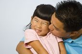 Asian father kissing daughter's cheek