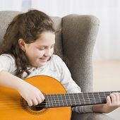 Hispanic girl playing guitar