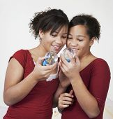 African twin sisters looking at snow globes