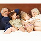 Late senior parents laying with two children on bed