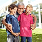 Happy grandfather with two grandchildren in a garden in front of a house