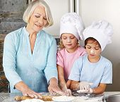 Two children cooking together with grandmother for christmas in a kitchen