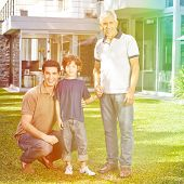 Smiling family in three generations in summer in a garden