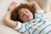 Mixed Race boy sleeping on sofa