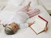 Asian woman reading on bed