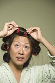Asian woman putting curlers in hair