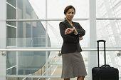 Hispanic businesswoman checking watch