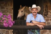 Hispanic man in front of stable