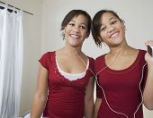 image of identical twin girls  - African twin sisters listening to same mp3 player - JPG