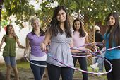 Hispanic girls playing with plastic hoops