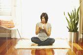 Asian woman drinking coffee on floor